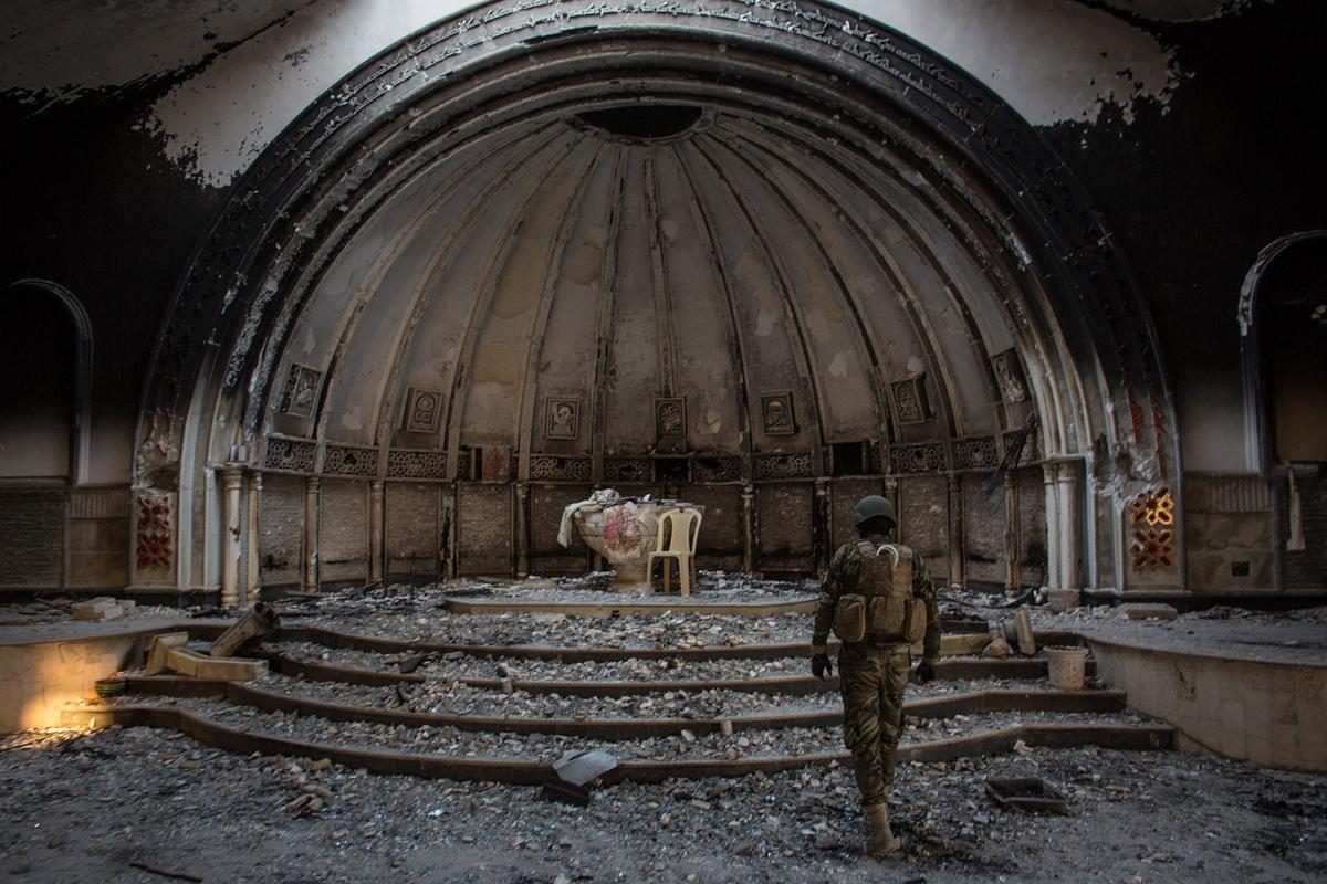مقاتل من NPU (وحدات حماية نينوى) يمر عبر كنيسة دمرت في 8 نوفمبر 2016 في الحمدانية. وNPU هي منظمة عسكرية تتكون من المسيحيين الآشوريين وتشكلت في أواخر عام 2014 للقتال ضد داعش.
