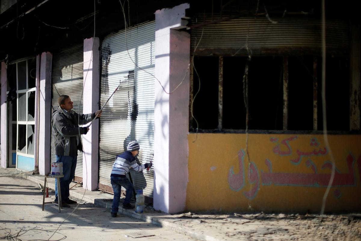 مسيحي عراقي وابنه يزيلان علامات وكتابات وضعها ارهابيي داعش على الجدران في 7 فبراير / شباط 2017.