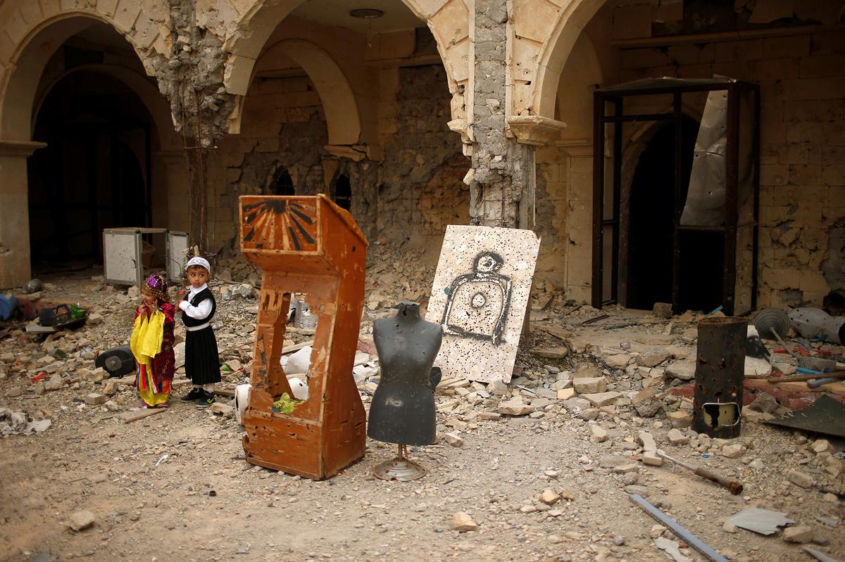 اطفال يزورون الكنيسة الرئيسية المحترقة حيث يحضر العراقيون قداس الأحد الأول في مدينة الحمدانية في 9 أبريل 2017.