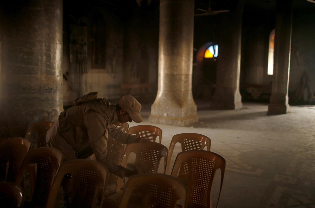 جندي عراقي ينظف الكراسي بينما يحضر المسيحيون اول قداس في الكنيسة الرئيسية المحترقة في مدينة الحمدانية منذ أن استعادتها القوات العراقية.