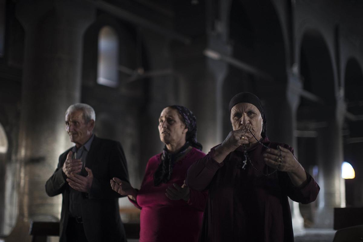المسيحيون العراقيون يصلون في كنيسة الحمل الطاهر، التي تضررت بسبب همجية داعش خلال احتلالهم للحمدانية.