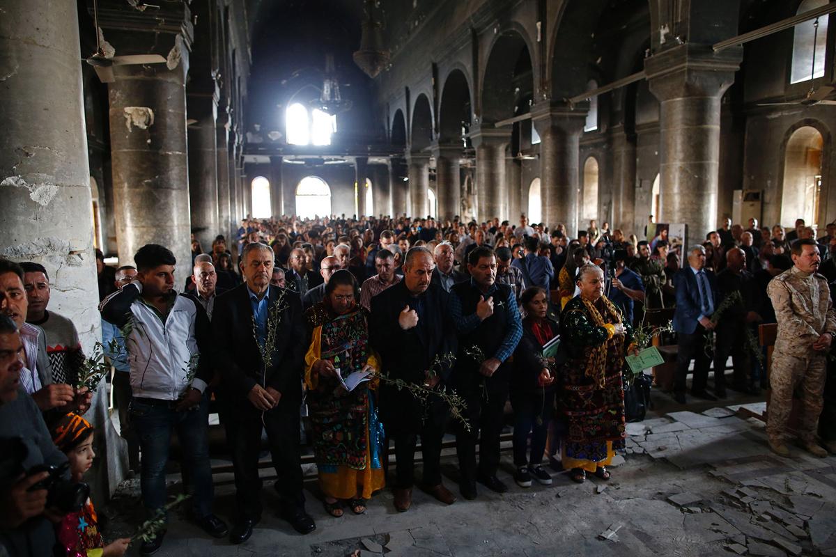 المسيحيون العراقيون يحضرون أول قداس يوم الأحد في 9 أبريل / نيسان 2017، في كنيسة الحمل الطاهر التي أصيبت بأضرار بالغة.