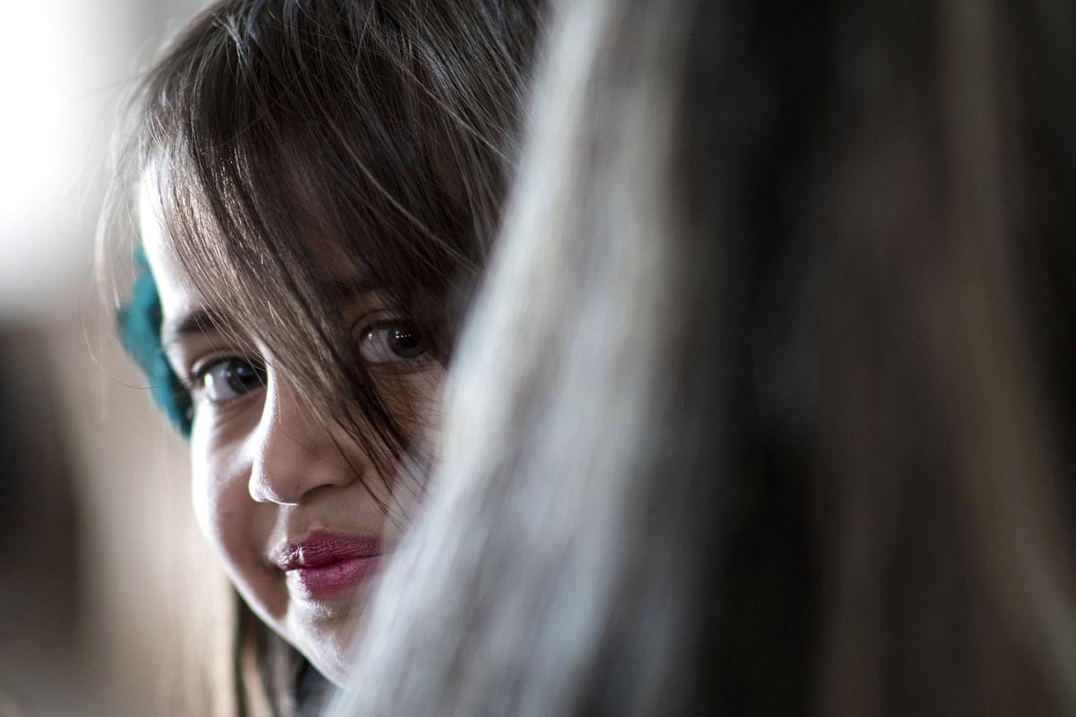 فتاة عراقية مسيحية سريانية تبتسم خلال موكب عيد الفصح في كنيسة القديس مار يوحنا في الحمدانية في 16 أبريل 2017.