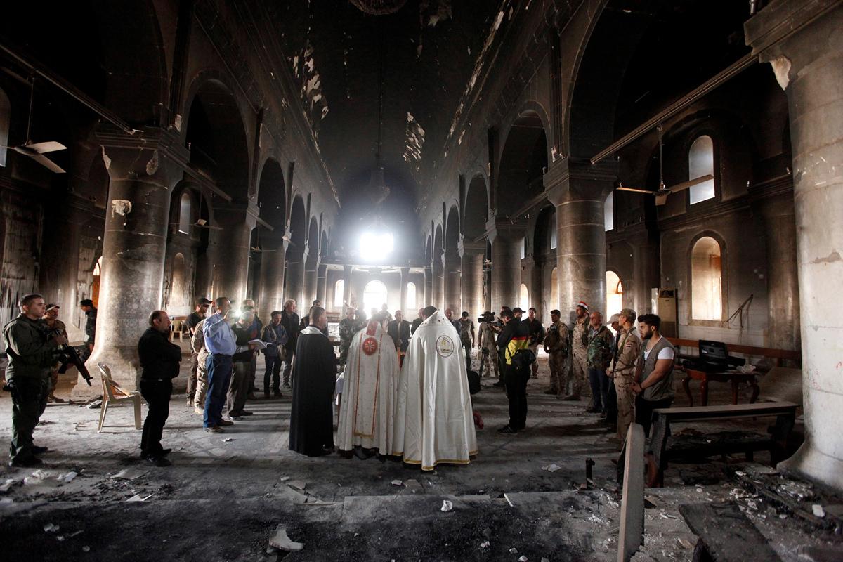 القساوسة العراقيين يحملون الكتلة الأولى في كنيسة تضررت ارضيتها خلال عملية اعادة الاعمار منذ أن تم استعادتها في 2 نوفمبر 2016.
