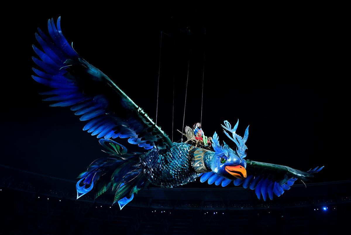 فتاة تركب على مجسم كبير لطائر العنقاء الاسطوري الشهير خلال حفل الافتتاح