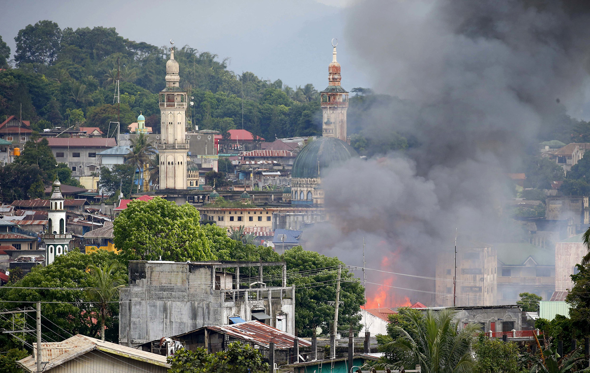 دخان يرتفع في حي سكني في مدينة مراوي حيث يستعر القتال بين جنود الحكومة وجماعة الموت المسلحة في 27 مايو 2017.