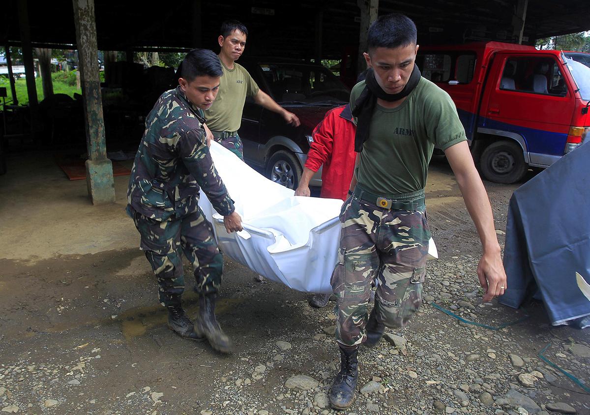 جنود يحملون احد القتلى من التنظيم الارهابي