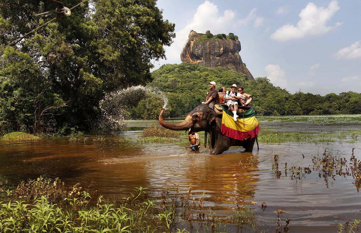 فيل يرش المياه على السياح الأجانب خلال رحلة سفاري في سيجيريا، على بعد حوالي 100 كيلومتر، شمال شرق كولومبو، سريلانكا، في 2 ديسمبر / كانون الأول 2011.