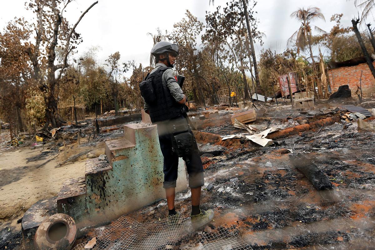 ضابط شرطة يقف في منزل أحرق خلال أيام العنف في مونغداو، بورما، في 30 أغسطس، 2017.