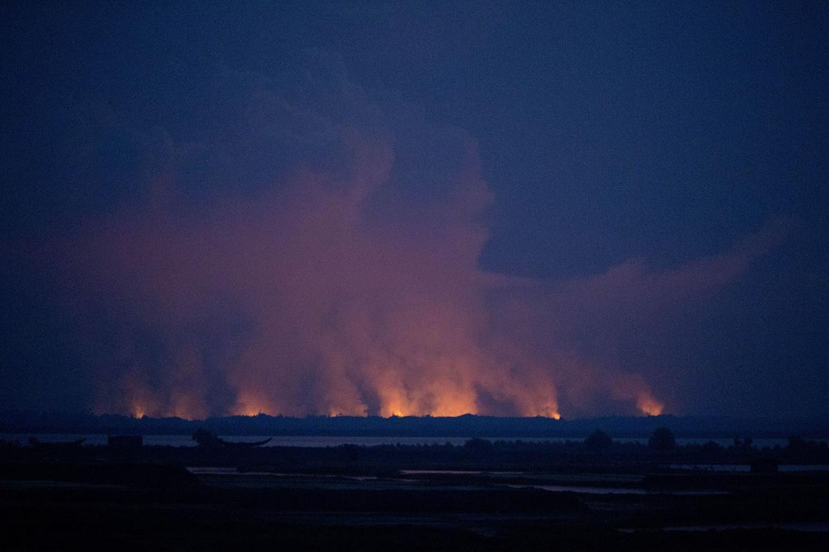 الدخان واللهب في بورما يمكن مشاهدته من الجانب البنغلاديشي من الحدود بالقرب من بازار كوكس في 3 سبتمبر 2017.  الآلاف من المنازل، وأحيانا قرى بأكملها يجري حرقها في الصراع الجاري في ولاية راخين ببورما.  ويلقي اللاجئون الروهينجا اللوم على قوات الجيش البورمية، بينما يدعي مسؤولون بورميون أن مسلحي الروهينجا هم المسؤولون عن العنف.  الوصول إلى المنطقة مقيد، لذلك التحقق المستقل أمر صعب.