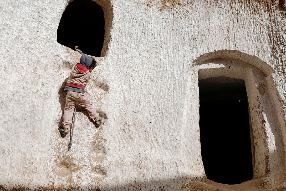أحلام، البالغة من العمر أربع سنوات، تتسلق حائطا للوصول إلى مخبأ أرنبها في منزل الكهف في ضواحي مطماطة في 5 فبراير 2018.