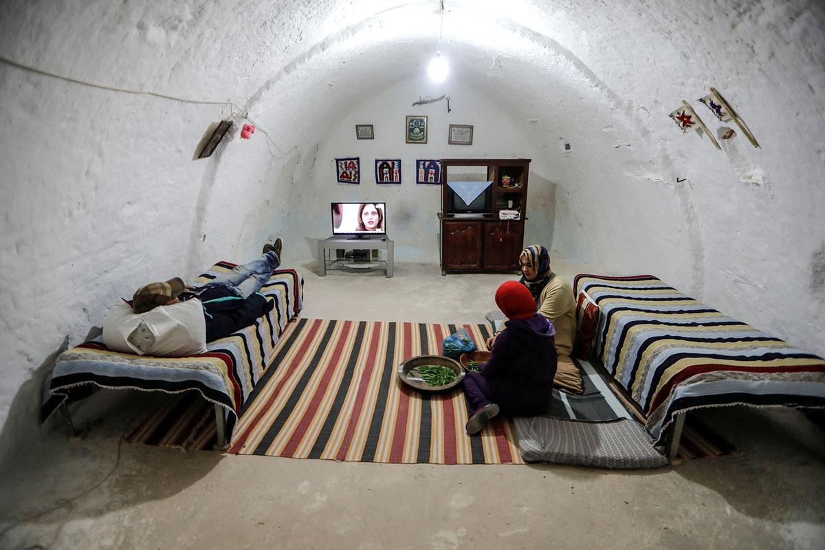 سمر، 18 سنة، ولطيفة بن يحي، 38 سنة، يقشرن البازلاء بينما يشاهد شقيقها التلفزيون في منزلهم تحت الأرض خارج مطماطة في 3 فبراير، 2018.