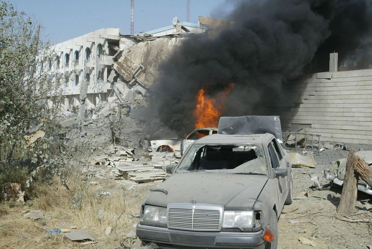 حريق يشتعل خارج مقر الأمم المتحدة في بغداد في 19 أغسطس / آب 2003. اثر انفجار سيارة مفخخة في المقر، مما أدى إلى تدمير جزء من المبنى.