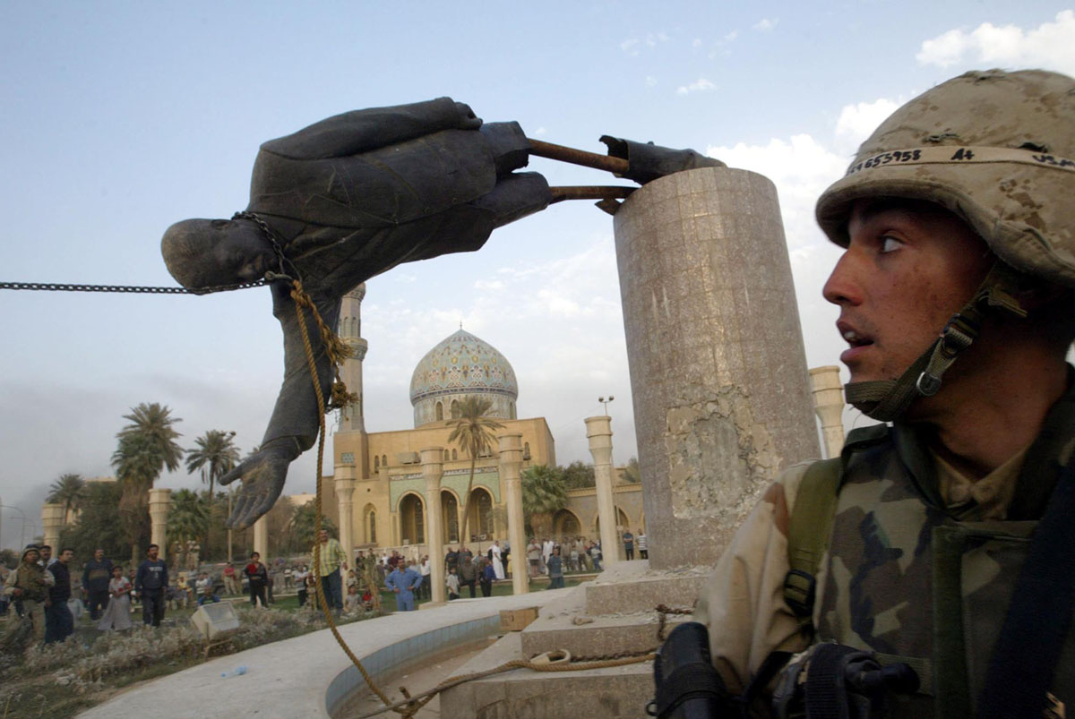 جندي أمريكي يقف مام تمثالاً للمقبور صدام حسين يقع في وسط بغداد في 9 أبريل/ نيسان 2003. وسحبت القوات الأمريكية تمثال صدام البالغ طوله 20 قدمًا.