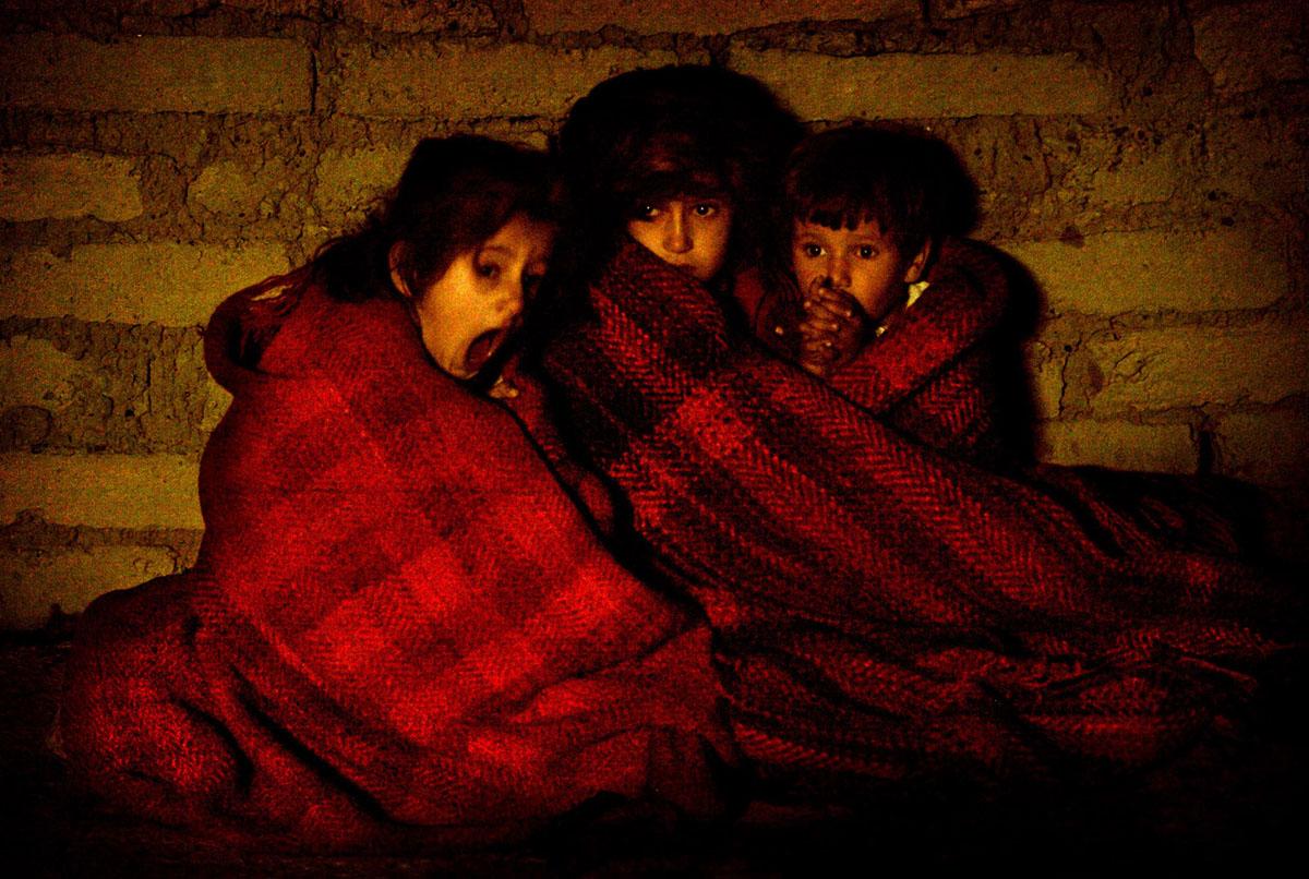 أطفال عراقيون مرعوبون يحمون أنفسهم من البرد بعد أخذهم خارج منزلهم خلال غارة قبل الفجر في إحدى ضواحي بعقوبة في 16 نوفمبر / تشرين الثاني 2003. اثناء البحث عن أعضاء خلية إرهابية مشتبه بها هاجمت قوات التحالف.  واحتجزت فرقة المشاة الرابعة التابعة للجيش عددًا من المسلحين بعد إطلاق النار على فريق هجوم أثناء العملية.