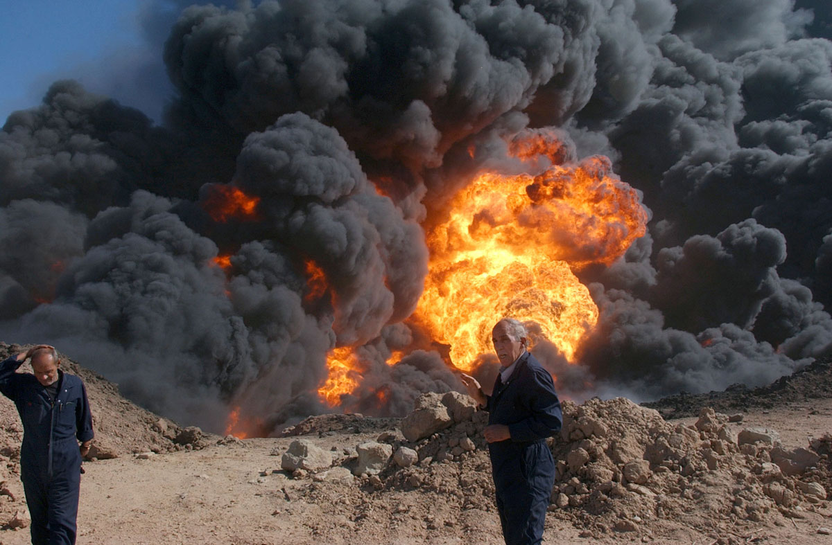 موظفوا وزارة النفط يحاولون اطفاء حريق اشتعل باحد انابيب النفط في كركوك سنة 2005