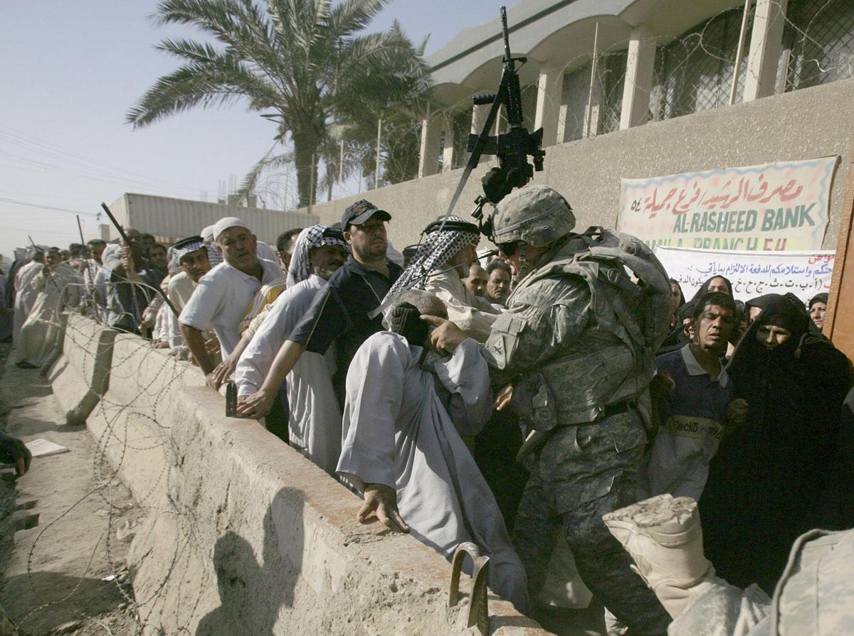الرقيب كايل هيل من يوكون، أوكلاهوما، الكتيبة 1-6، اللواء الثاني، الفرقة المدرعة الأولى، تضرب رجلاً خارج بنك الرشيد في سوق جميلة بمدينة الصدر، بغداد، في 10 يونيو 2008.