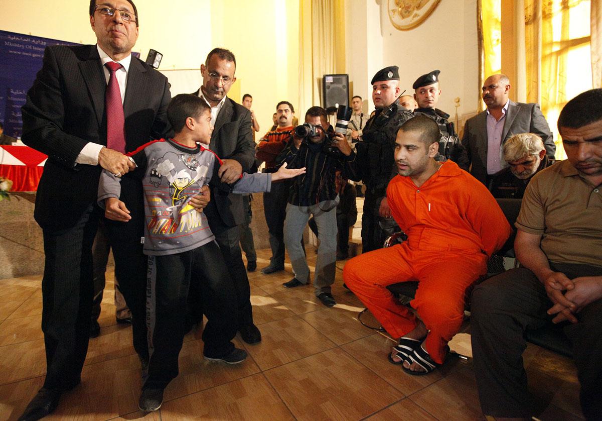 صبي عراقي امام شخص من المتشددين، واتُهم بقتل والده في ذروة الحرب الطائفية ضد الشيعة في عام 2006 حتى عام 2007، أثناء تقديم المتهم إلى وسائل الإعلام في وزارة الداخلية ببغداد في 21 نوفمبر/ تشرين الثاني 2011. تم تقديم 22 متشددًا مشتبهًا إلى وسائل الإعلام أثناء انتظار محاكمتهم.