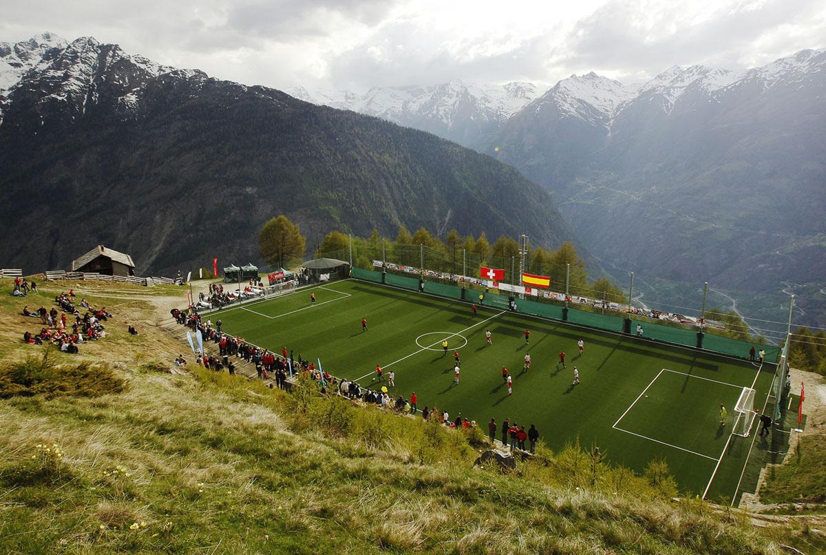 لاعبو نادي إف سي جسبون (الأبيض)، ممثل سويسرا، يلعبون ضد إف سي زوما (الأحمر)، ممثلين لإسبانيا ، خلال مباراة كرة القدم الدولية في قرى الجبال في جسبون، في جبال الألب السويسرية، في 29 مايو 2010. يتم لعب المباراة على أعلى ملعب لكرة القدم مرتفعة في أوروبا. في حوالي 2000 متر، لا يمكن الوصول إلى الملعب إلا بواسطة التلفريك، والذي لا يمكن أن يحمل سوى 10 أشخاص، أو سيرا على الأقدام - تسلق 45 دقيقة.