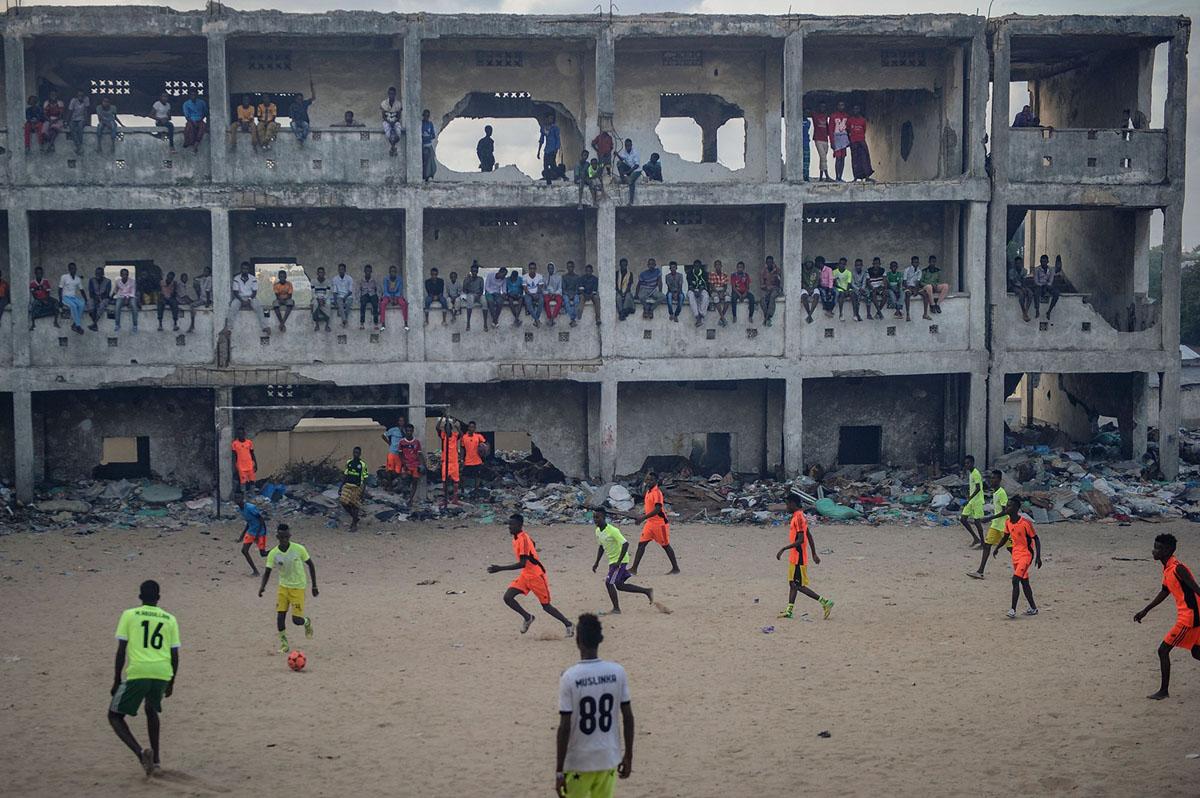 شباب صوماليون يلعبون كرة القدم في الهواء الدخاني، بسبب حرق القمامة في مدرسة ثانوية مدمرة ومهجورة، في مقديشو بالصومال، في 7 يونيو 2018.