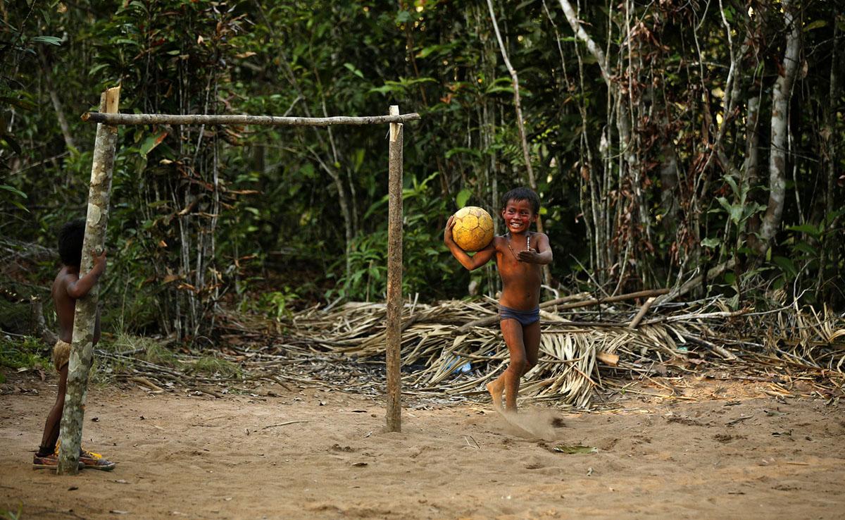 أعضاء قبيلة تاتويو الأمازونية يلعبون في قريتهم في ريو نيغرو بالقرب من مدينة ماناوس ، في 23 يونيو 2014.