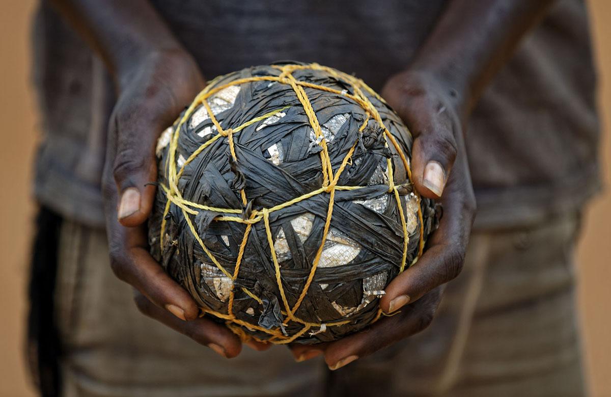 هذه الصورة التقطت بتاريخ 3 يونيو 2017، يحمل صبي لاجئ من جنوب السودان كرة قدم مؤقتة أثناء لعبه مع أصدقائه في مستوطنة بيدي بيدي للاجئين في شمال أوغندا. توجد ملاعب كرة القدم ومسابقات بين القرى عبر أكبر مستوطنة للاجئين في العالم. يتم إنشاء المزيد  مما يؤكد أهمية الرياضة في مجتمع يحاول أن ينسى أهوال الحرب بمصدر ترفيهي نادر في وجود كئيب آخر.