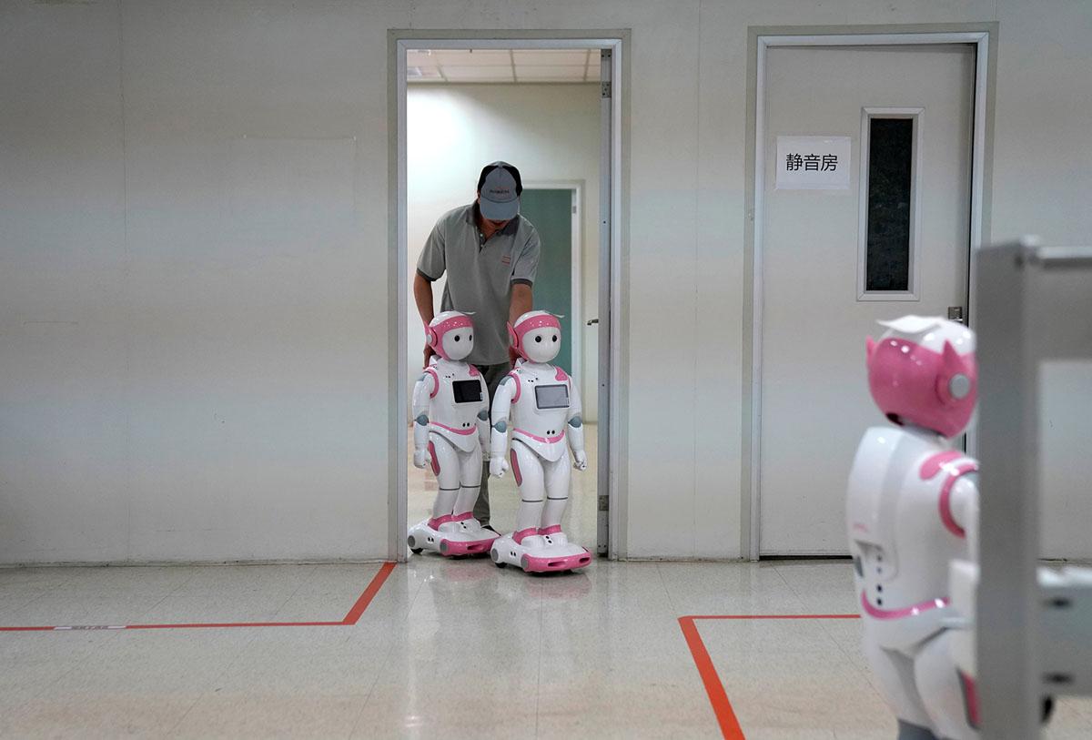 عامل يضع اللمسات الأخيرة على الروبوتات الاجتماعية iPal، التي صممها AvatarMind، في مصنع تجميع في سوتشو بمقاطعة جيانغسو، الصين، في 4 يوليو 2018.  مصممة لتقديم التعليم والرعاية والمرافقة للأطفال والمسنين، 3.5 قدم الروبوتات طويل القامة رشيقة تأتي في الجنسين ويمكن أن تحكي القصص والتقاط الصور وتقديم محتوى تعليمي أو ترويجي.