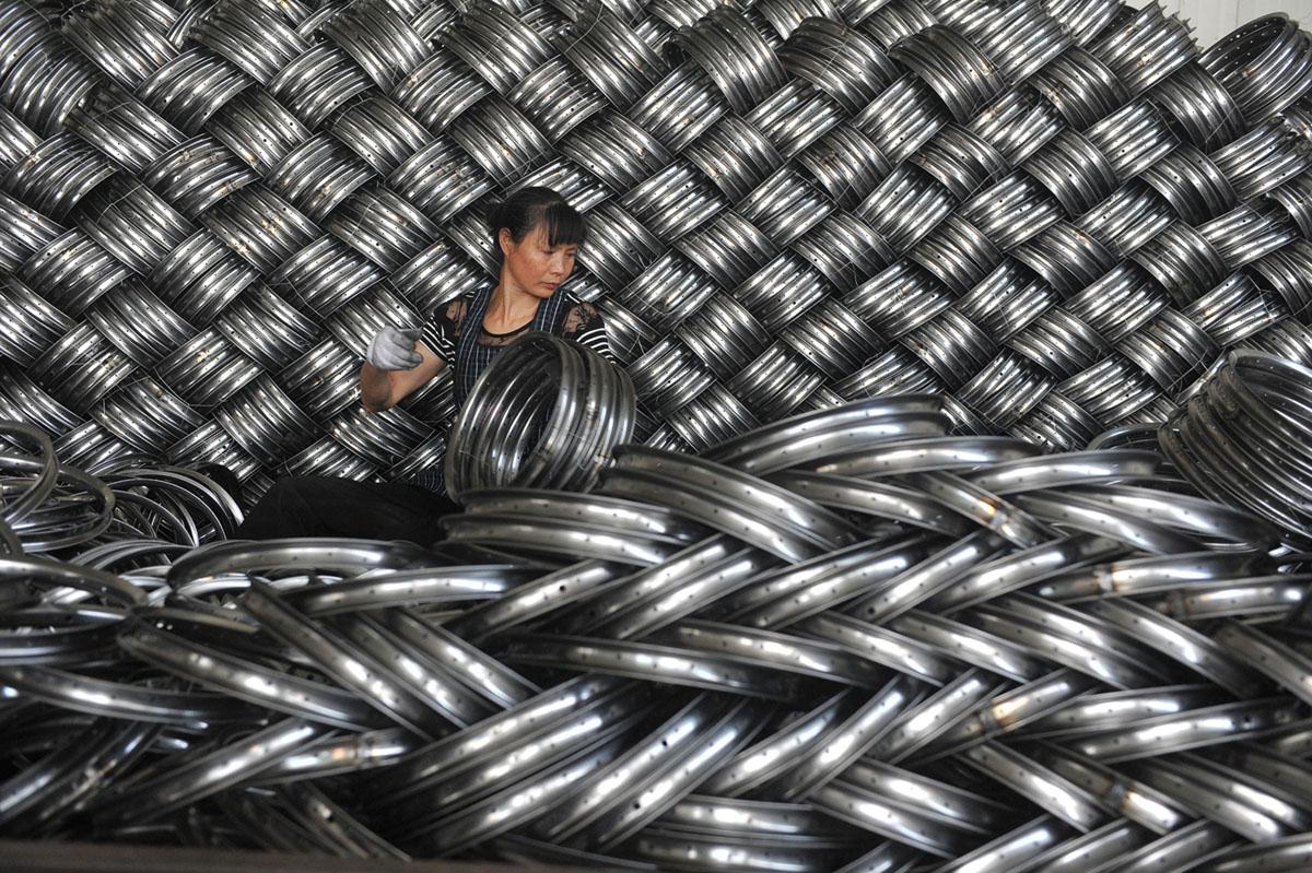 امرأة تعمل على تغليف إطارات دراجات فولاذية للتصدير في ورشة تصنيع الشركة المصنعة للمعدات الرياضية في مدينة هانغتشو بمقاطعة تشجيانغ، في 4 يونيو، 2018.