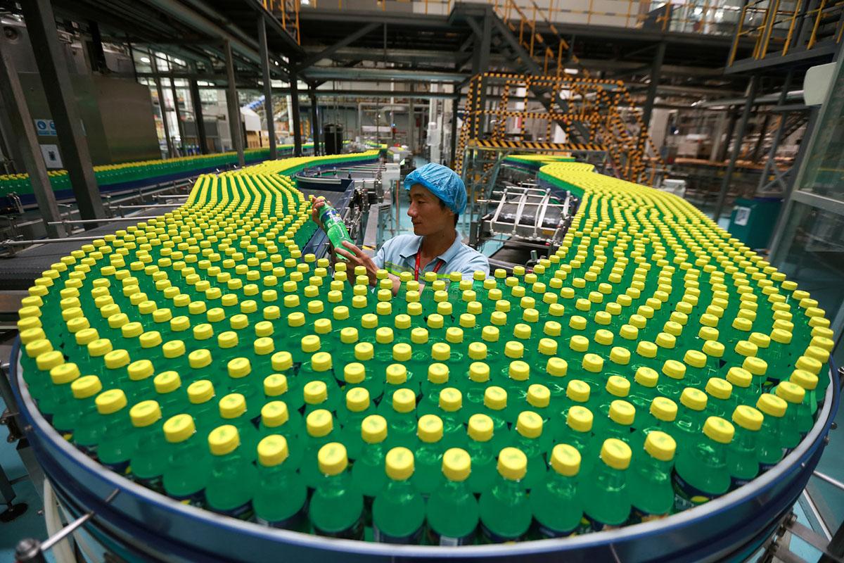 موظف يفحص زجاجة مشروب عند خط إنتاج مصنع في لوهي، مقاطعة خنان، في 15 أغسطس 2016.