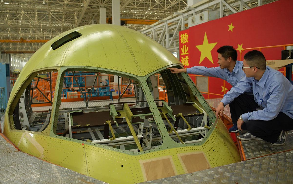 يقوم الفنيون بفحص الجزء الأمامي من ثالث طائرة ركاب محلية الصنع C919 ذات الممر الواحد في الصين قبل أن تغادر المصنع في 4 مايو 2017 في تشنغدو بمقاطعة سيتشوان.