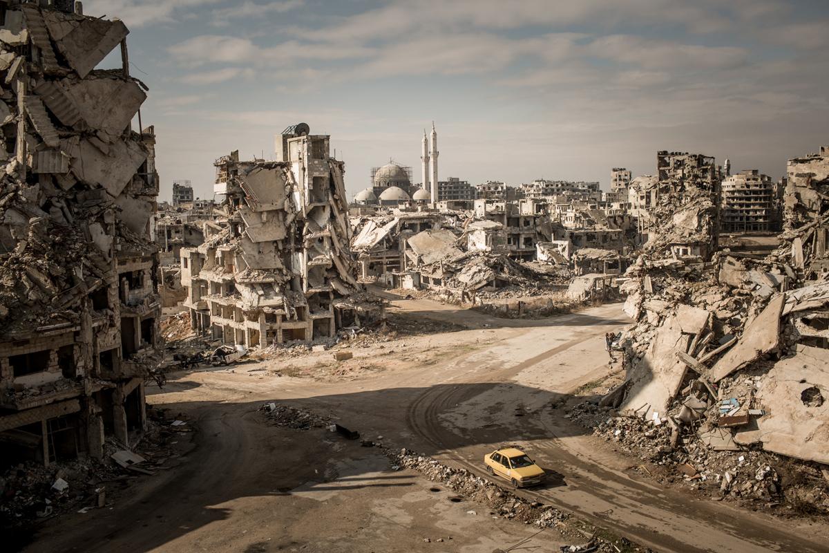 المركز الثالث، الأماكن: أثناء مهمتنا في دير شبيجل، قمنا برحلة على الطريق عبر سوريا لتوثيق الوضع الحالي في المدن الكبرى. عندما دخلت حي الخالدية لأول مرة في حمص، صدمت. لم أشاهد مثل هذا الدمار واسع النطاق من قبل، وكنت قد زرت العديد من المدن المدمرة. كانت المنطقة المحيطة بحي الخالدية هادئة للغاية. لا أصوات في المدينة، ولا سيارات، لا شيء. فقط النقيق من يبتلع الصمت والرياح. نزلنا في شوارع الخالدية، لكن الدمار كان واسع الانتشار لدرجة أنه لم يكن بإمكانك الحصول على الصورة الكبيرة من الشارع - يمكنك فقط الاحاطة برؤية من الأعلى. لتصوير هذه الصورة، سألت جندي سوري مسؤول عن المنطقة هل اتمكن من التسلل إلى الخراب. وافق الجندي على السماح لي بالتسلق على مسؤوليتي الخاصة. تسلقت أنقاض منزل سابق - كان مليئا بالأجهزة المتفجرة المرتجلة - وأخذت الصورة. كنت محظوظا جدا لالتقاط الصورة عندما كنت على السطح. بدون أي علامة للحياة، كانت صورة ميتة. يمكنني تذكر المشهد بشكل واضح.
