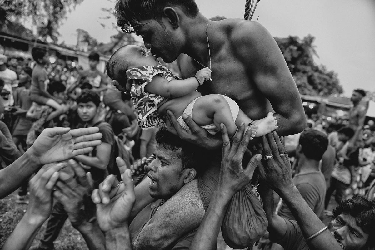 المركز الثالث، الناس: هندوسي يقبل مولوده الجديد خلال مهرجان Charak Puja في غرب البنغال، الهند. وتدعو الممارسة التقليدية إلى أن يُخترق المحب بمشبك وأحيانًا يتدلى من حبل. هذه التضحية المؤلمة تتم لإنقاذ أطفالهم من القلق. أثناء تغطيتها للمهرجان ، تمكنت من عرض الممارسة الدينية من وجهة نظر المصلين الهندوس. حاولت التقاط لحظة الحب والارتباط بين الأب وولده، وأظهر اهتمام الأب بابنه الصغير.