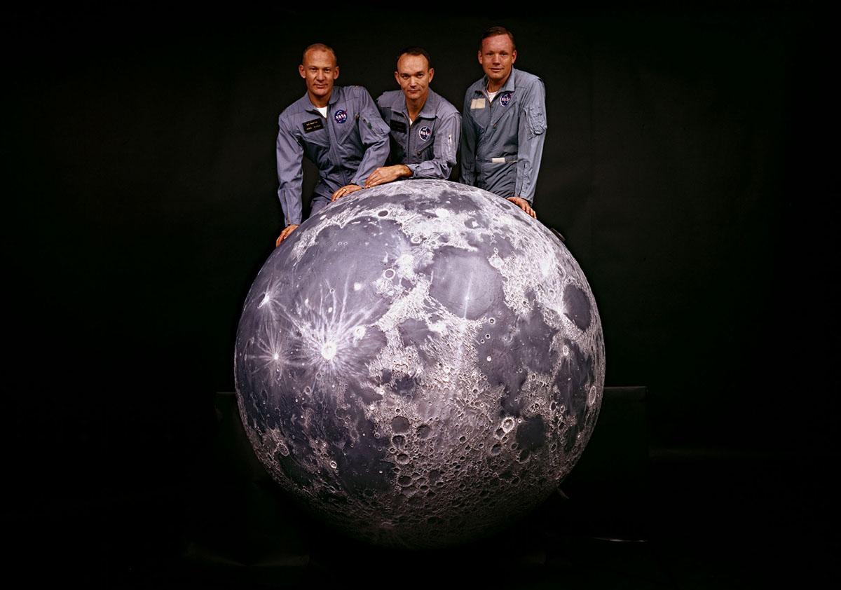 صورة لطاقم بعثة أبولو 11 التابعة لناسا إلى القمر؛ من اليسار، رواد الفضاء باز ألدرين، مايكل كولينز، ونيل أرمسترونج، وهم يطرحون نموذجًا للقمر في عام 1969.