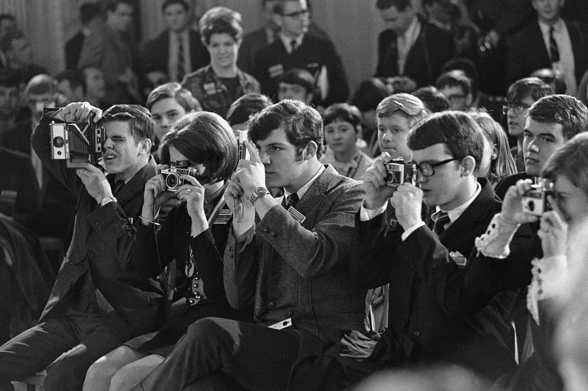 يلتقي الطلاب الذين يحضرون اليوم الأخير من منتدى الشباب بمجلس الشيوخ الأمريكي في 8 فبراير، 1969 في واشنطن العاصمة، مع الرئيس نيكسون، ويستخدمون كاميراتهم لتسجيل الزيارة.