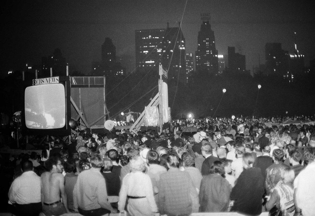 يراقب حشد من الناس طاقم أبوللو 11 على القمر، على شاشات الفيديو العملاقة في سنترال بارك في نيويورك في 20 يوليو 1969.