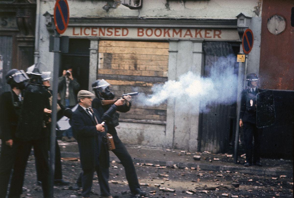 رجال شرطة يرتدون أقنعة واقية من الغازات قنابل الغاز المسيل للدموع أمام متجر مراهنات خلال أعمال الشغب في أولستر في لندنديري، أيرلندا الشمالية، في 12 أغسطس 1969.