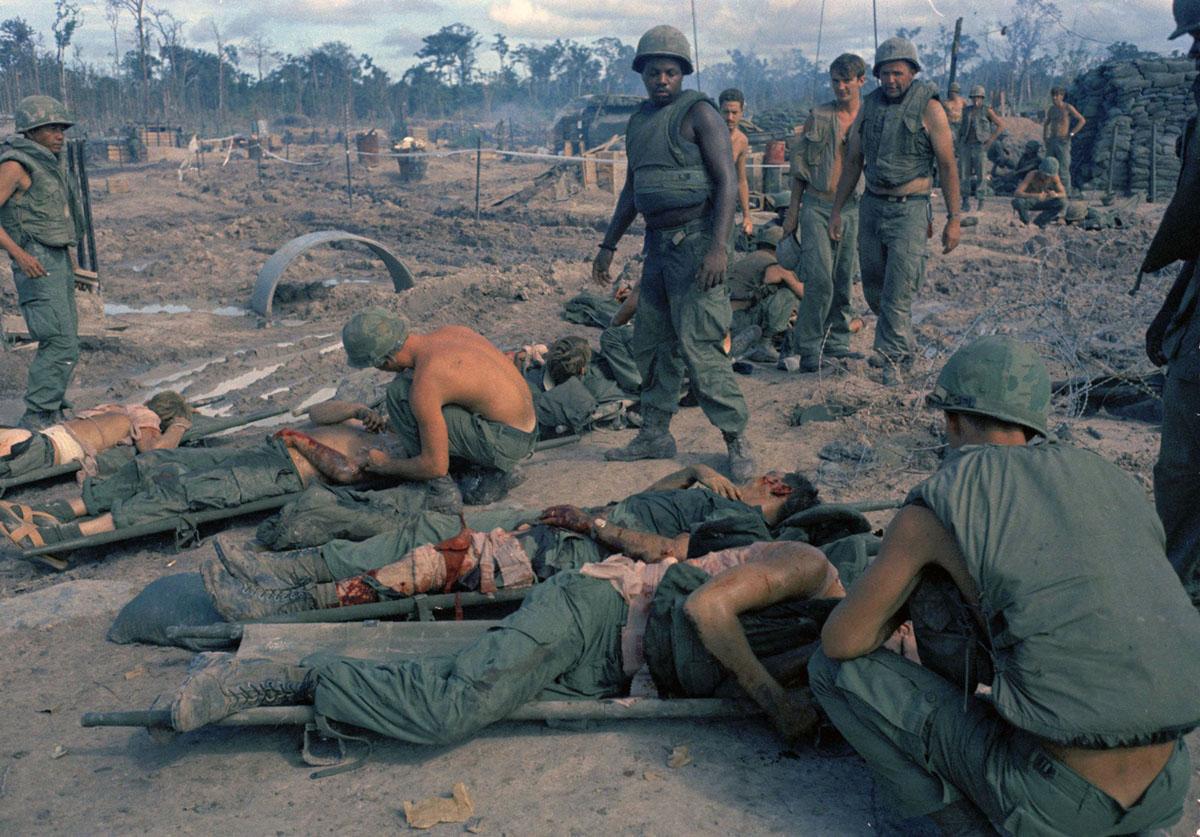 جنود فرقة الجيش الأمريكي الأولى من سلاح الفرسان في العراء بعد أن جرحوا في هجوم صاروخي بقذائف الهاون وقذائف الهاون على قاعدة إيك النارية، على بعد حوالي 60 ميلاً من سايغون ، فيتنام ، في 5 سبتمبر 1969.