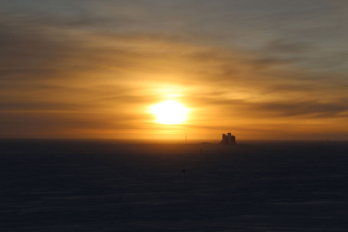 شروق الشمس في محطة Amundsen-Scott South Pole في 26 سبتمبر 2018. المبنى في الافق هو تلسكوب IceCube neutrino.