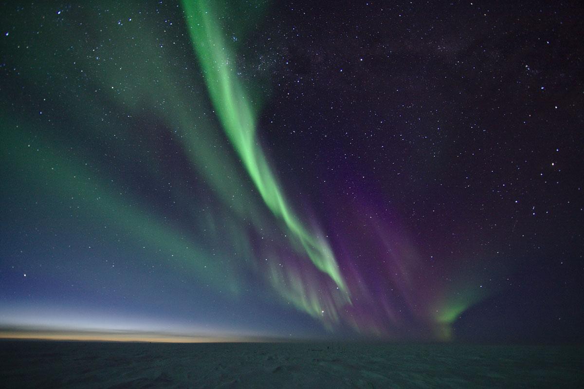 تتشكل الأنوار القطبية (الشفق القطبي الشمالي/ الشفق الأسترالي) عندما تتعرض الجسيمات المشحونة المنبعثة من الشمس إلى المجال المغناطيسي للأرض وتصطدم بالذرات والجزيئات في غلافنا الجوي. ويتطلب رصدها سماء مظلمة بشكل تام دون تلوث وجو واضح. وهذا يجعل القطب الجنوبي في أنتاركتيكا مكانًا ممتازًا للتجارب التي تلاحظ وتميز الأضواء القطبية. تم التقاط الصورة بتاريخ 13 آب 2017.