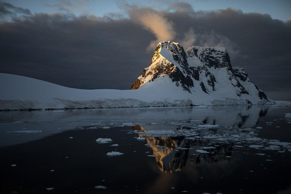 تنعكس الأنهار الجليدية والمنحدرات في مياه قناة لومير بالقرب من جزيرة بوث في 8 فبراير، 2019.