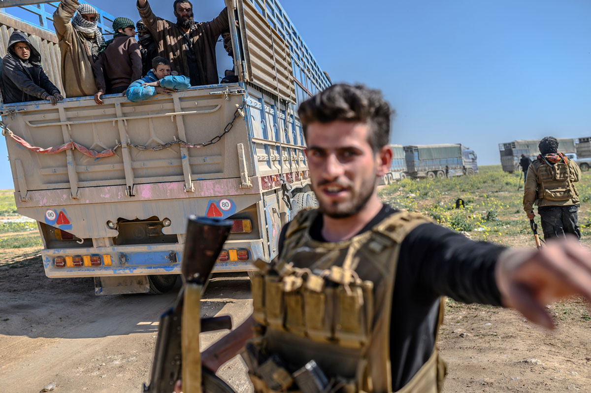 يراقب أحد عناصر قوات الديمقراطية السورية التي يقودها الأكراد شاحنات تقل مجموعة من تنظيم داعش استسلموا، أثناء نقلهم من آخر معقل التنظيم في بلدة باغوز في شمال محافظة دير الزور، 20 فبراير، 2019.