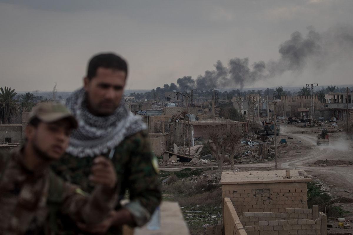 الدخان يتصاعد فوق مباني اثر غارة جوية خلف جنود قوات الدفاع الذاتى على سطح بالقرب من الخط الأمامي في 10 فبراير 2019 ، في باغوز.