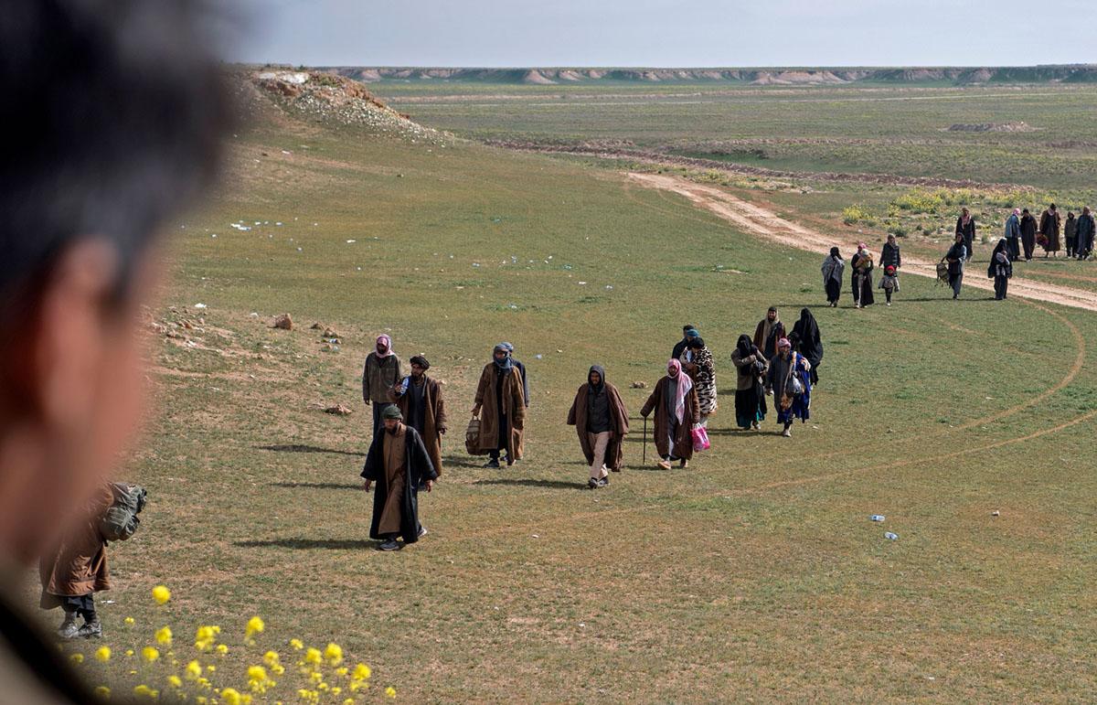 عناصر من تنظيم داعش وعائلاتهم يسيرون في حقل أثناء مغادرتهم التنظيم المتعثرة في باغوز في 13 فبراير، 2019.