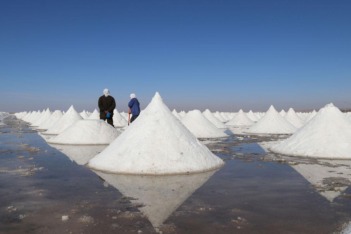 يعمل عدد من الأشخاص في أكوام الملح بمنطقة التبخر في بحيرة مالحة في محافظة غاوتاي بمقاطعة قانسو بشمال غرب الصين، في 31 أكتوبر عام 2018. ويعود تاريخ هذا المنجم إلى أكثر من ألفي عام.