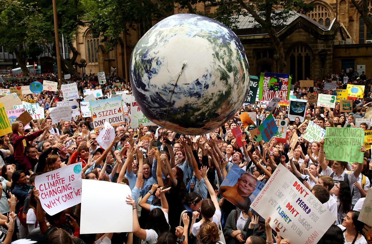 بالون يمثل كوكب الارض حوله حشد من المتظاهرين خلال تجمع للتغير المناخي في قاعة مدينة سيدني في أستراليا في 15 مارس 2019.