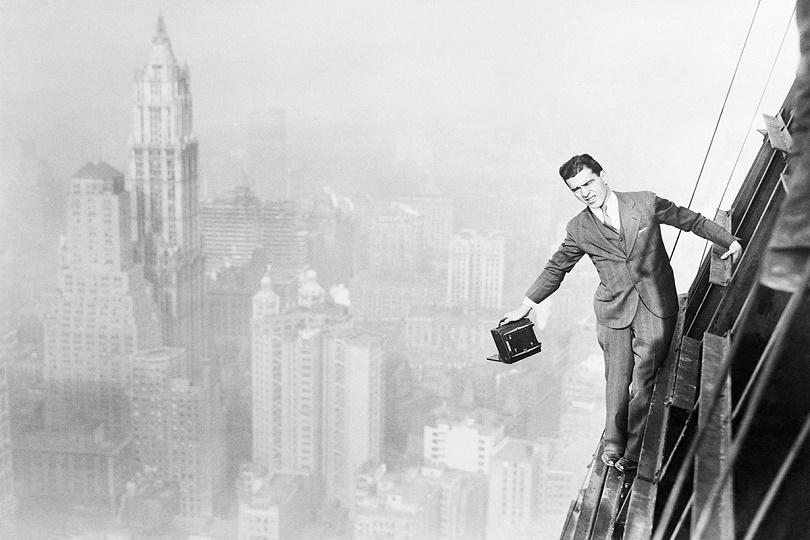 جاك رايلي ، المصور الجريء، من أطول مبنى في العالم ، هيكل بنك مانهاتن المكون من 74 طابقًا ، قيد الإنشاء في وول ستريت في مدينة نيويورك. يظهر فيها قسم الأعمال البارز في نيويورك في الخلفية ، حيث يوجد مبنى Woolworth في الجزء العلوي الأيسر.