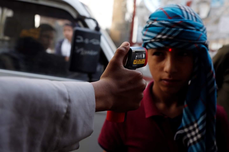 تظهر الصور أحد العاملين في مجال الصحة وهو يفحص درجة حرارة جسم فتى قبل دخوله مسجد في العاصمة اليمنية، صنعاء.
