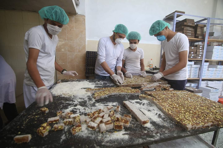 فلسطينيون يصنعون حلوى تركية داخل متجر قبل عيد الفطر، الذي يصادف نهاية شهر رمضان، في مدينة رفح بجنوب قطاع غزة في 7 مايو عام 2020.
