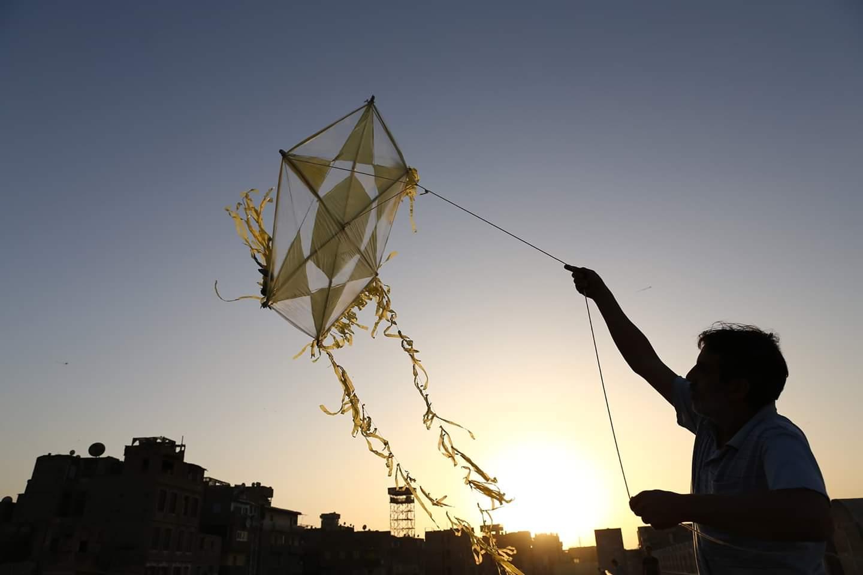 أشخاص يطيرون طائرات ورقية على سطح مبنى للتغلب ملل العزل وسط جائحة كوفيد-19 في القاهرة، مصر، في 11 مايو 2020.