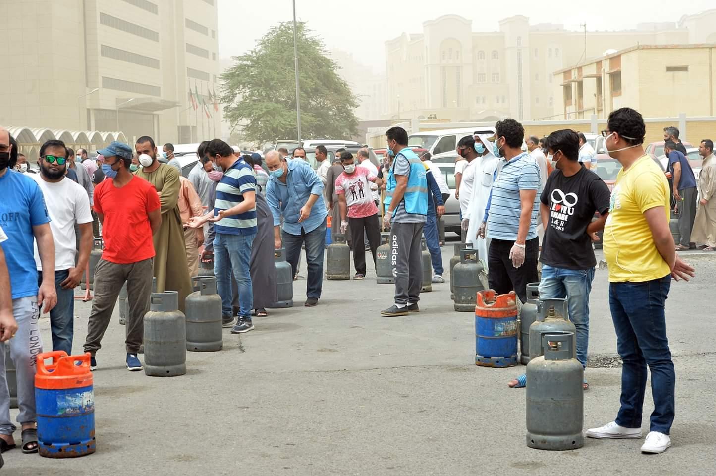أناس يتجمعون أمام مركز لتوزيع الغاز في محافظة حولي بالكويت يوم 10 مايو 2020. وأعلنت الحكومة الكويتية في وقت متأخر من يوم الجمعة حظر تجوال كاملا فى البلاد لمدة ثلاثة أسابيع للحد من الارتفاع السريع في حالات الإصابة بفيروس كورونا الجديد.